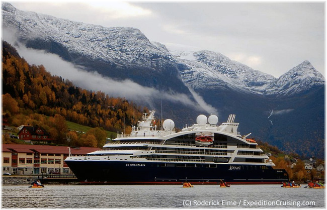 Ponant Le Champlain tied up at Olden, Norway as guests kayak in the fjord (Photo credit: Roderick Eime)